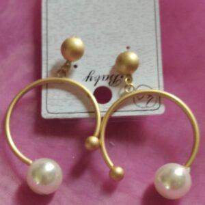 Boucle d'oreille grande créole ouverte couleur beige mat avec une grosse perle blanche brillante